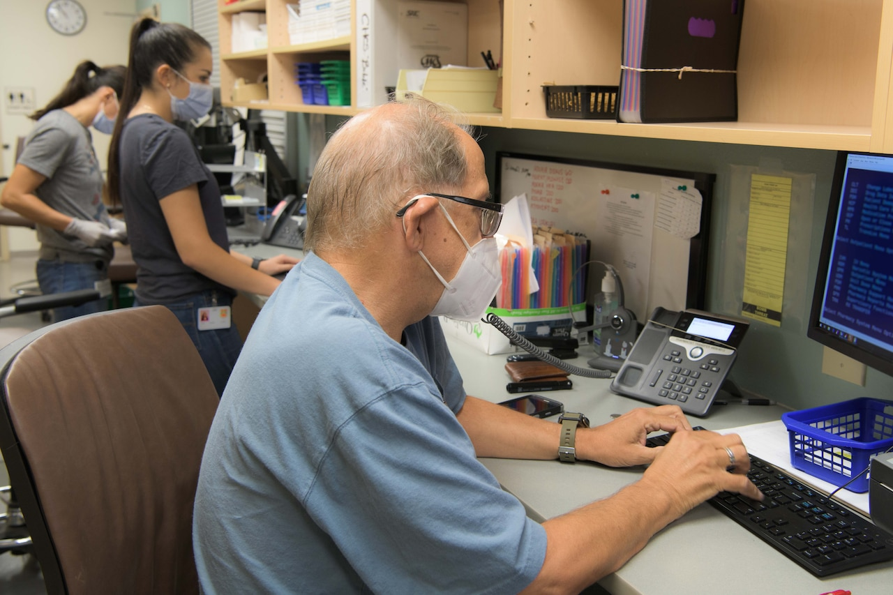 A man wears a face mask while working on a computer.