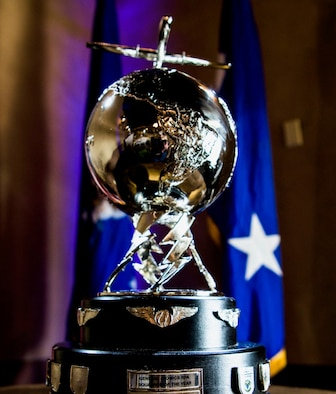 A trophy with a silver globe and lightning bolts displayed on top of 2 black tier circles with military flags draped in the back ground.