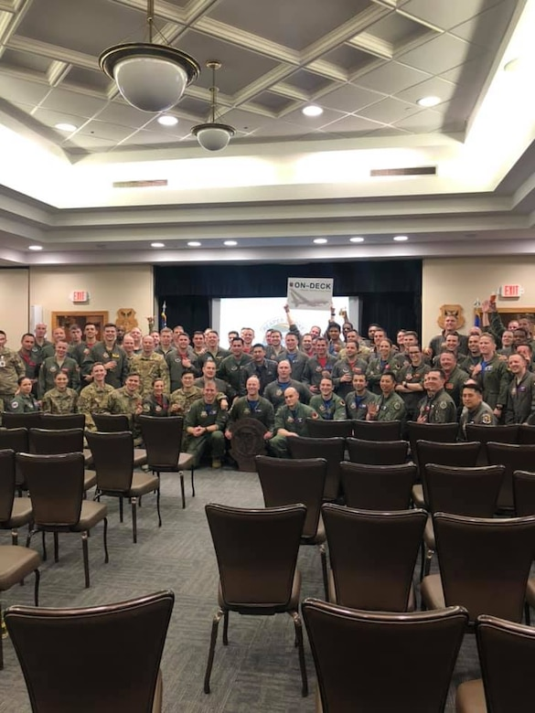 68 military members, in uniform, pose indoors at a lecture hall and holding a squadron emblem in the center of the photo with all smiles in celebration.