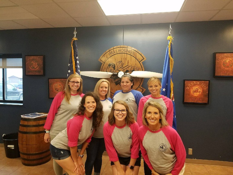 7 females spouses wearing matching squadron baseball shirts pose as a group while looking at the camera.