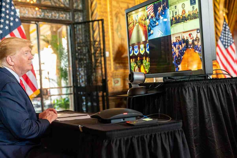 President Trump sitting at a table and looking at a monitor with images from 5 different locations of military members ranging from 5 to 15 people looking back at the president while having a conversation.