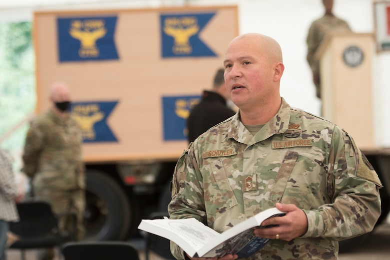 A photo of an Airman reading a creed from a book
