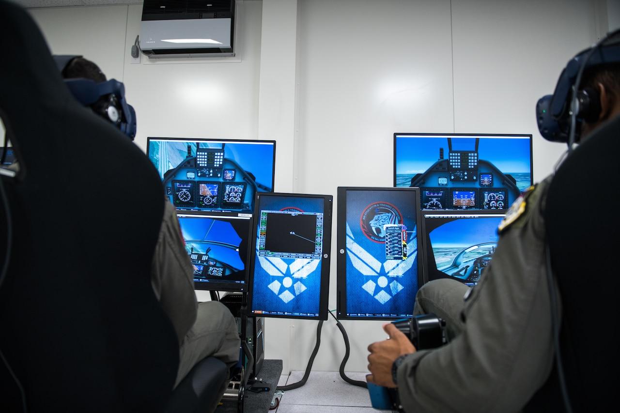 Airmen operate an aircraft simulator.