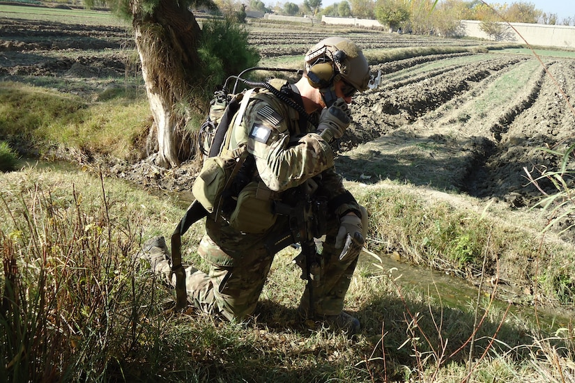 A soldier is down on one knee in a field.