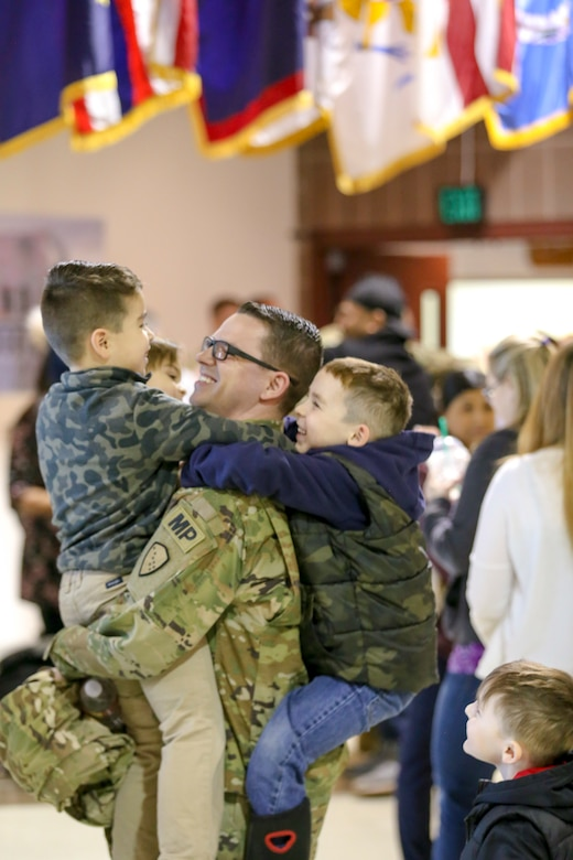 Alaska Army Guardsmen from the 297th Military Police Company visit with friends and family members following a deployment ceremony at the Alaska National Guard Armory on Joint Base Elmendorf-Richardson, Alaska, March. 13, 2019. Approximately 80 Alaska Guardsmen from the 297th Military Police Company are deploying to the U.S. Central command area of responsibility in support of Operations Spartan Shield for about nine months. (U.S. Army National Guard photo by 2nd Lt. Balinda O'Neal Dresel)