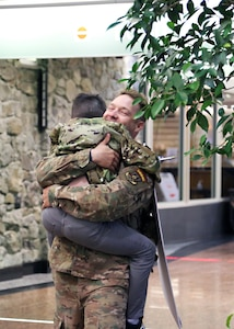 TSgt. Severin Stalmarck , an airman with the 176th Security Forces Squadron, embraces his son at Ted Stevens-Anchorage International Airport upon his return from Kandahar, Afghanistan on June 22, 2020. 12 AKNG Airmen deployed in support of Operation Freedom Sentinel, a NATO-led continuation of the Global War on Terrorism. (U.S. Air National Guard photo by Lt. Col. Candis Olmstead/Released)