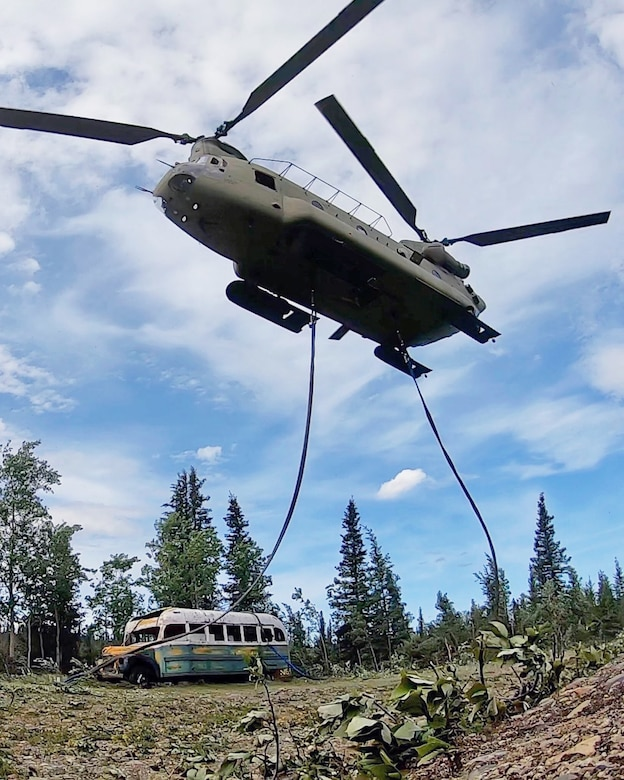 "Alaska Army National Guard Soldiers assigned to 1st Battalion, 207th Aviation Regiment execute an extraction mission via a CH-47 Chinook helicopter over Healy, Alaska, June 18, 2020. As part of a combined effort with the Department of Natural Resources, the Guardsmen rigged and airlifted ""Bus 142"",, an historic icon from book and film, ""Into the Wild"", out of its location on Stampede Road in light of public safety concerns. The bus will be stored at a secure site while the DNR considers all options and alternatives for its permanent disposition. (Alaska National Guard courtesy photo)"