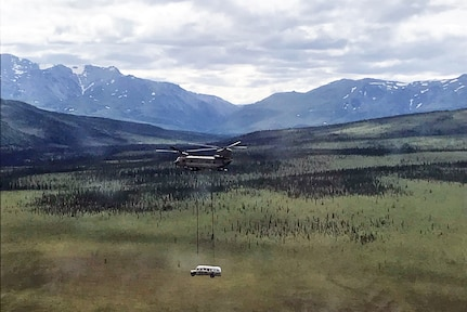 """Alaska Army National Guard Soldiers assigned to 1st Battalion, 207th Aviation Regiment execute an extraction mission via a CH-47 Chinook helicopter over Healy, Alaska, June 18, 2020. As part of a combined effort with the Department of Natural Resources, the Guardsmen rigged and airlifted """"Bus 142"""",, an historic icon from book and film, """"Into the Wild"""", out of its location on Stampede Road in light of public safety concerns. The bus will be stored at a secure site while the DNR considers all options and alternatives for its permanent disposition. (Alaska National Guard courtesy photo)"""