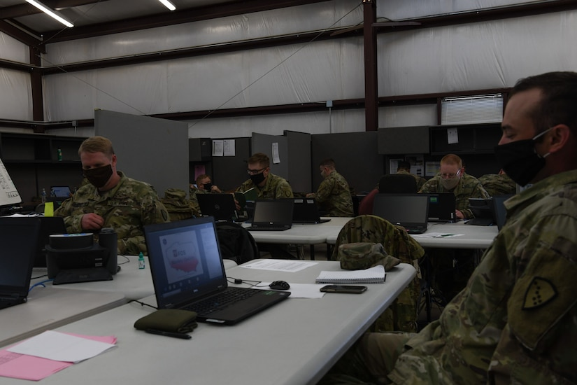 Alaska Army National Guard Soldiers are separated into forward operating sites by tables and dividers during this exercise, to replicate the separation they will face while In Poland during a training exercise at Fort Hood, Texas, May 25, 2020. Simulated separation will force them to contact other locations via. email or telephone.  (U.S. Army National Guard Photo by SGT Heidi Kroll)