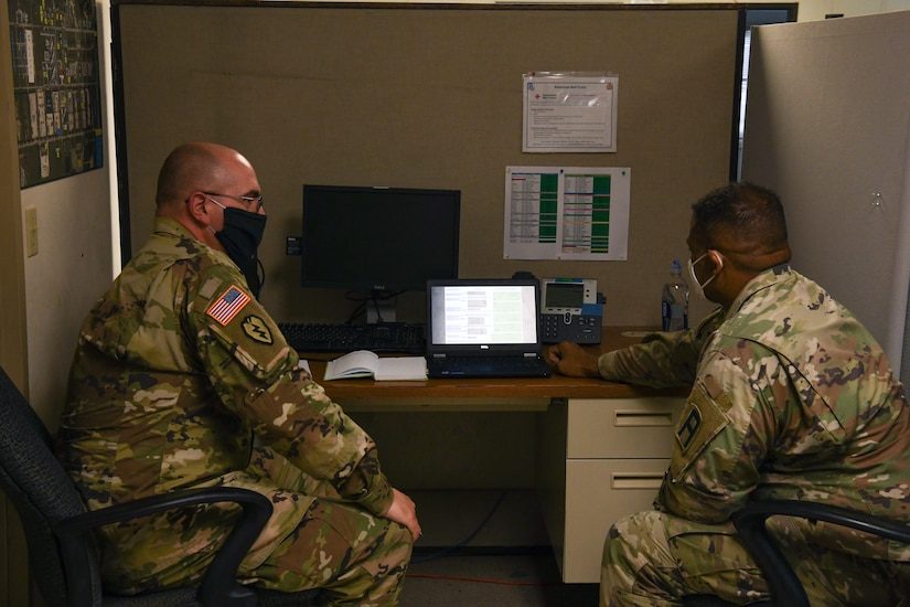 Alaska Army National Guard Sergeant Charles Medlin, 297th Regional Support Group, works with Sergeant 1st. Class Arthur Washington,120th Headquarters, Headquarters company Infantry Battalion, to go over his chaplain assistant duties while in Poland at Fort Hood, Texas, May 25, 2020. Chaplains Assistants are responsible for working with Soldiers in regards to their individual faiths, and making sure their religious needs are met. (U.S. Army National Guard Photo by SGT Heidi Kroll)