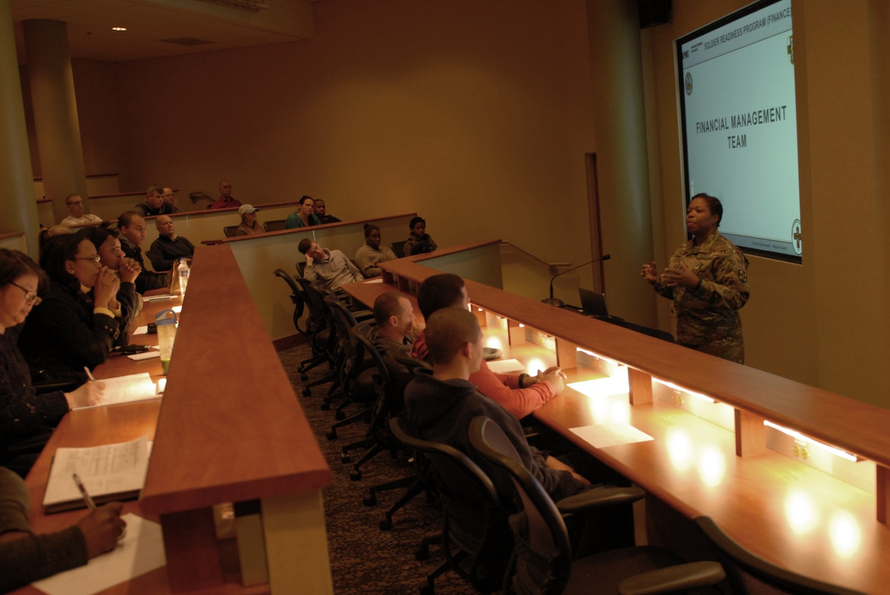 Soldiers in a large room listen to a woman speak.