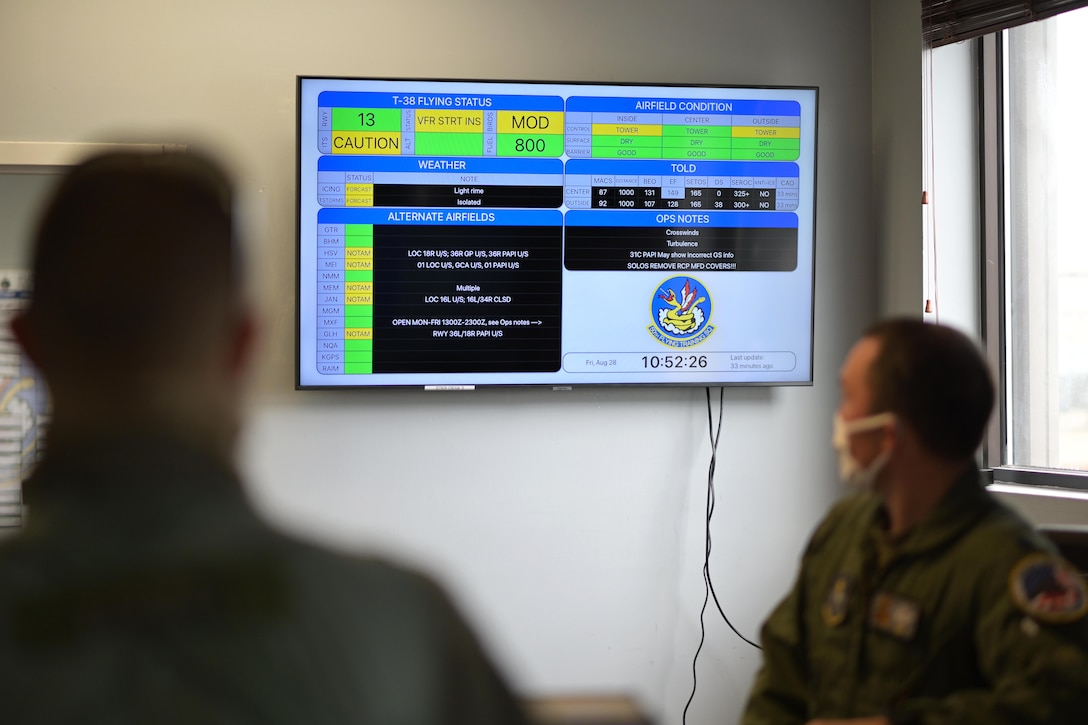 A pilot from the 50th Flying Training Squadron checking the airfield conditions at the step desk, August 28, 2020, on Columbus Air Force base, Miss. Pilots use the AF Status application readily available at the step-desk to check on weather conditions, alternate airfields and other pertinent information. (U.S. Air Force photo by Senior Airman Jake Jacobsen)