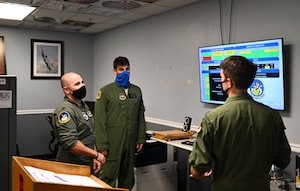 Capt. Mckenzie Kane (left), 50th Flying Training Squadron instructor pilot, Capt. Anthony Olive (middle), 50th FTS student pilot and Capt. Kirk Jaunich (right), 50th FTS student pilot discuss the benefits of the AF Status application August 24, 2020, on Columbus Air Force base, Miss. Along with the AF Status application Kane designed other programs that focus on helping pilots gather information in an easy to read and functional format way. (U.S. Air Force photo by Senior Airman Jake Jacobsen)