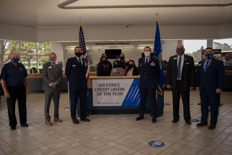 U.S. Air Force Col. Zachery Jiron, third from left, 60th Air Mobility Wing vice commander, Lt. Col. Andrew Wilkins, third from right, 60th Comptroller Squadron commander, and the Travis Credit Union staff stand around an Air Force Credit Union of the Year sign during the 2019 Air Force Distinguished Credit Union Award presentation Sept. 9, 2020, at Travis Air Force Base, California. Travis Credit Union earned the Air Force Distinguished Credit Union Award in recognition of the achievements they made over the course of a year. (U.S. Air Force photo by Senior Airman Cameron Otte)