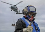 Aviation boatswain's mate (handling) 3rd class Tainesha Hines shows encouragement on flight deck during vertical replenishment onboard amphibious assault ship USS Makin Island, Pacific Ocean, April 20, 2020 (U.S. Navy/Harry Andrew D. Gordon)