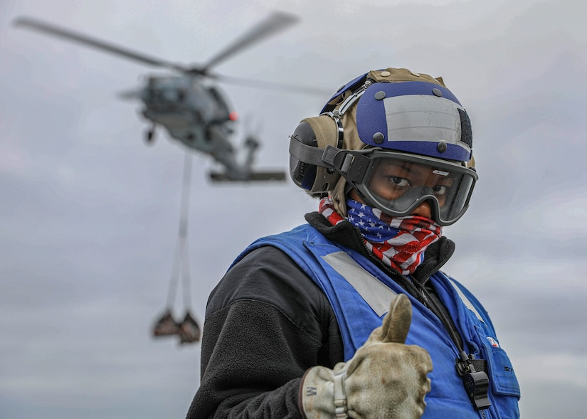 Aviation boatswain's mate (handling) 3rd class Tainesha Hines shows encouragement on flight deck during vertical replenishment onboard amphibious assault ship USS Makin Island, Pacific Ocean, April 20, 2020 (U.S. Navy/Harry