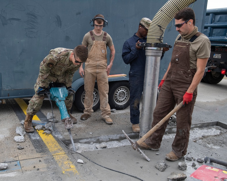 U.S. Air Force Airmen from the 52nd Civil Engineer Squadron pavements and construction equipment shop use a jackhammer on concrete at Spangdahlem Air Base, Germany, Sept. 10, 2020. The Airmen, known as the Dirt Boyz, consistently perform repairs to the flightline to ensure the 52 FW mission can be accomplished. (U.S. Air Force photo by Airman 1st Class Alison Stewart)