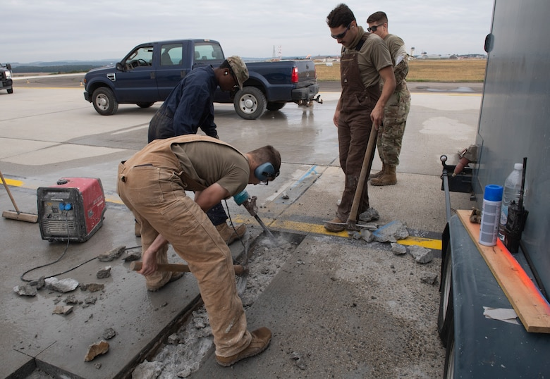 U.S. Air Force Airmen from the 52nd Civil Engineer Squadron pavements and construction equipment shop use a jackhammer on concrete at Spangdahlem Air Base, Germany, Sept. 10, 2020. The Dirt Boyz fixed two large cracks on the flightline which prevented obstructions caused by foreign object debris. (U.S. Air Force photo by Airman 1st Class Alison Stewart)
