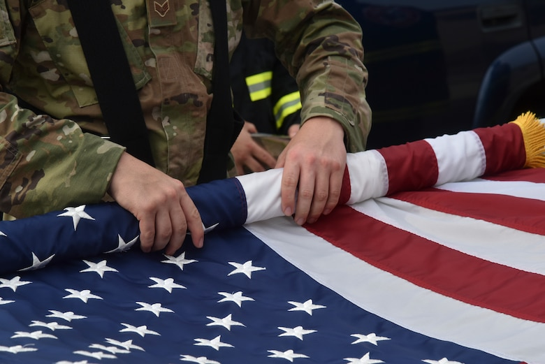 An honor guardsman rolls the American Flag after a 9/11 memorial service on Kunsan Air Base, Republic of Korea.