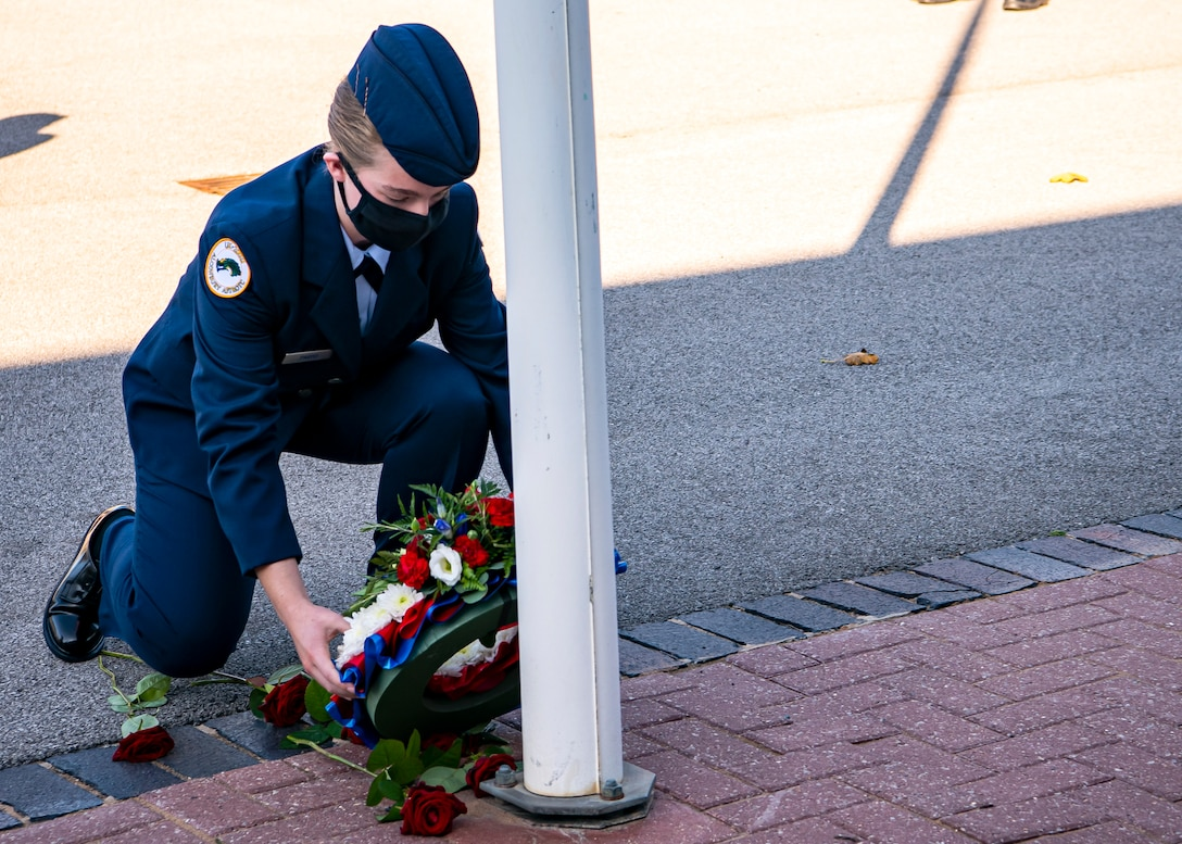 Emily Pardo, Alconbury High School JROTC cadet, places a wreath next to a flagpole during a 9/11 remembrance ceremony at RAF Alconbury, England, Sep. 9, 2020. Cadets along with Airmen from the 501st Combat Support Wing participated in the ceremony to honor those who lost their lives during the September 11th terrorist attacks. (U.S. Air Force photo by Senior Airman Eugene Oliver)