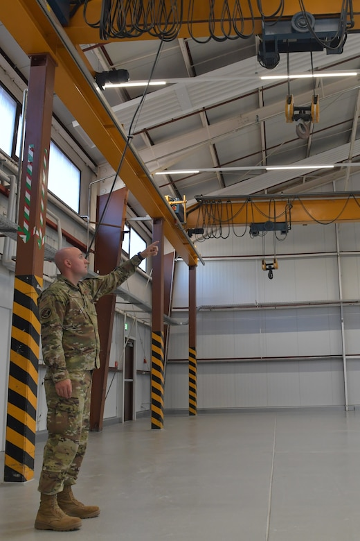 An Airman points to a hoist hanging in a maintenance facility.