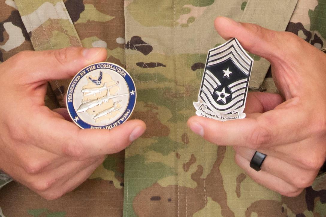 A close-up of two coins being held by an Airman.