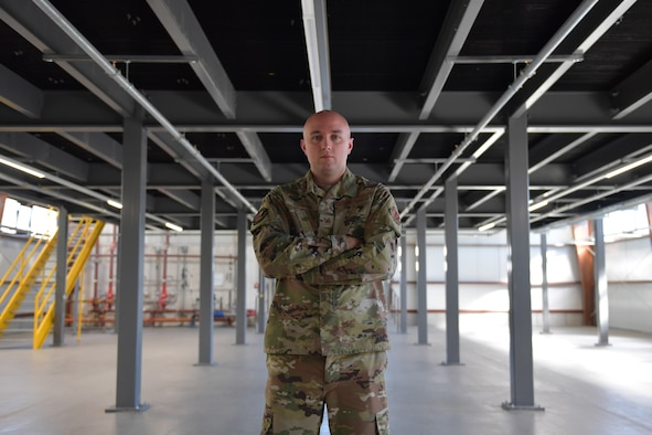 An Airman points to a mezzanine in a maintenance facility.