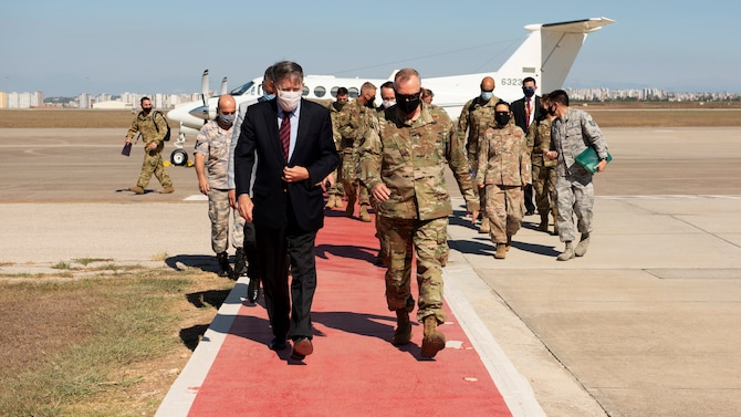 """Col. John Creel, 39th Air Base Wing commander, and U.S. Ambassador to Turkey David Satterfield walk down the flight line """"red carpet"""" with retinue in-tow behind them."""