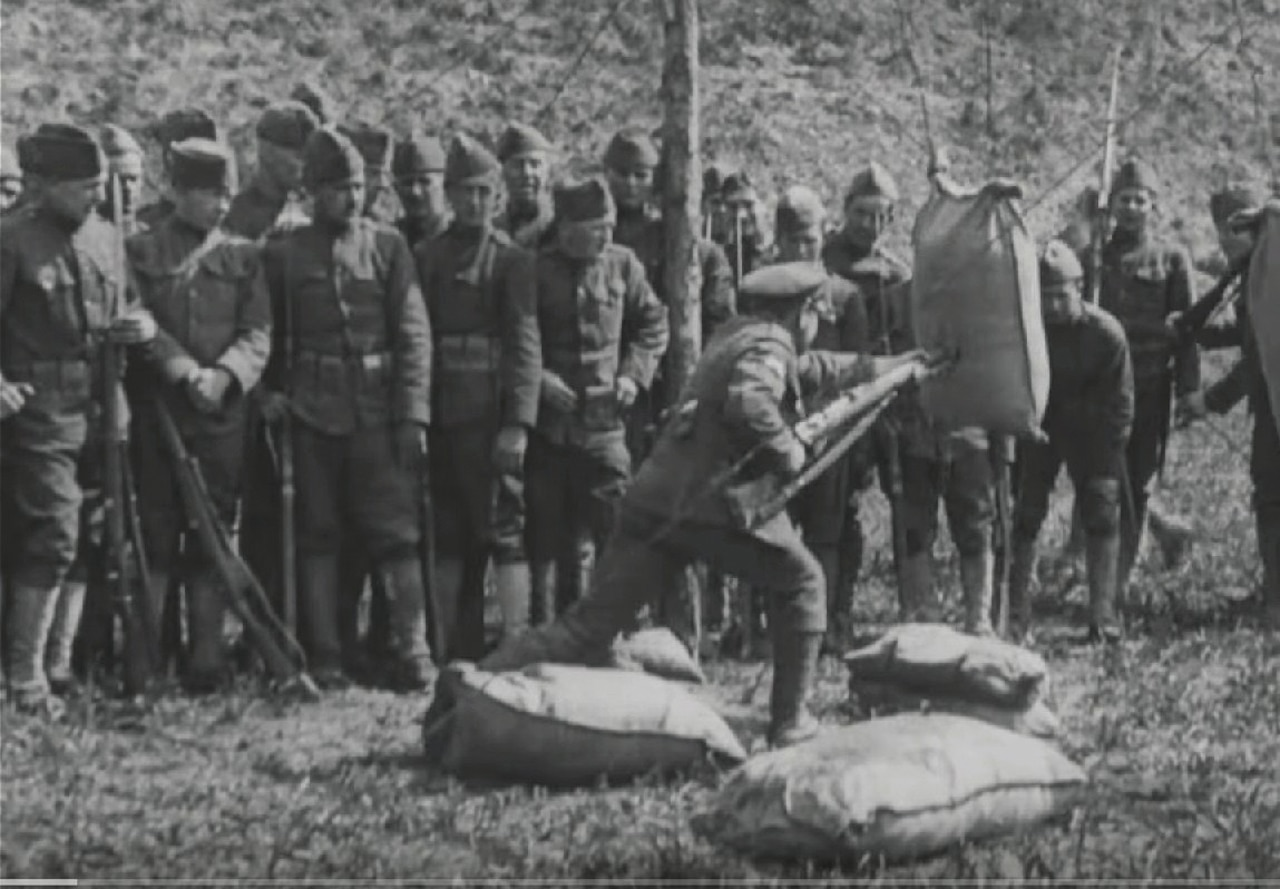 A man stabs a stuffed sack with a bayonet as others watch.
