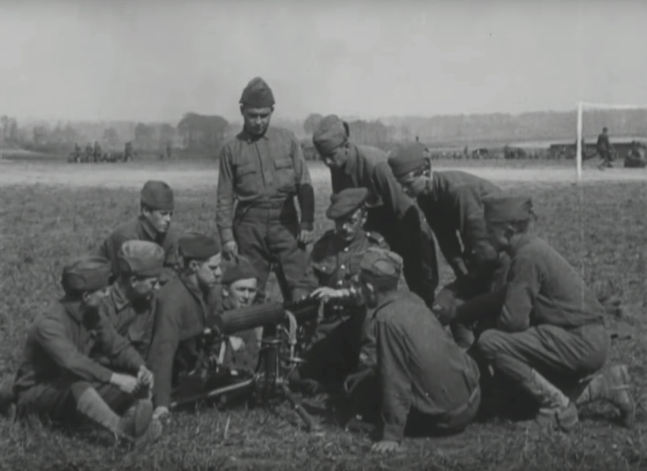 Several men surround a machine gun as they closely watch its operator.