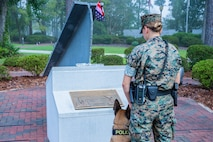 U.S. Marine Lance Cpl. Zoey Proffitt, a military working dog handler assigned to Security Company, Headquarters & Support Battalion, and military working dog Ddrago pay their respects in remembrance of the fallen heroes and victims of the events on Sept. 11, 2001 at the 9/11 Memorial in the Lejeune Memorial Gardens on Marine Corps Base Camp Lejeune, N.C., Sept. 11, 2020. The 9/11 Memorial includes a beam from the Twin Towers, presented by police and firefighters of New York in honor of the first troops deployed in the Global War on Terror from the base.