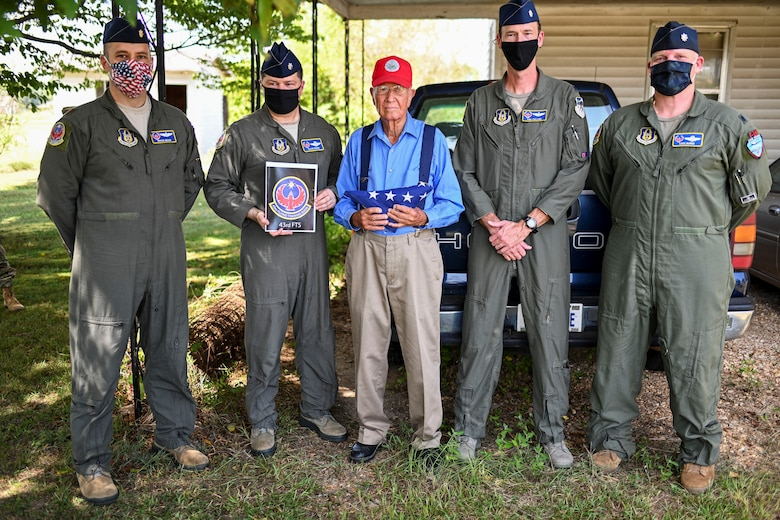 Bradford Freeman, assigned to 'Easy' Company, 2nd Battalion of the 506th Parachute Infantry Regiment of the 101st Airborne Division, stand with members from the 43rd Flying Training Squadron at Freeman's residency Sept. 3, 2020 in Miss. The 43rd FTS flew an American Flag in each trainer airframe over Columbus Air Force Base, Miss. and raised the flag outside Freeman's House in honor of his service and sacrifice to the U.S. (U.S. Air Force photo by Senior Airman Keith Holcomb)