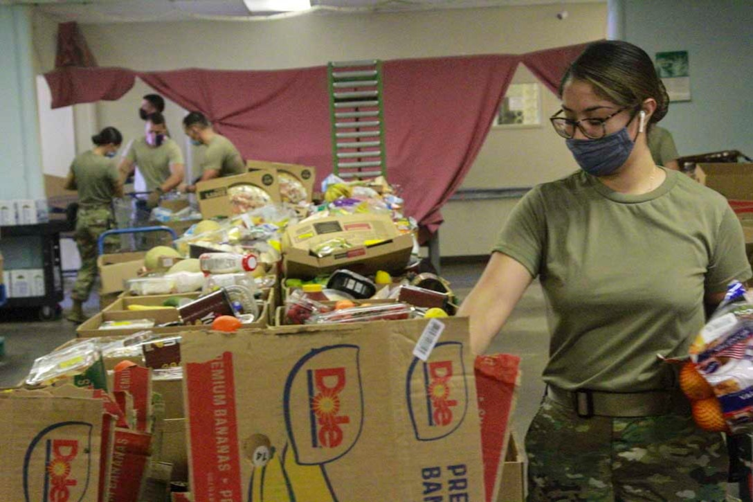 A soldier wearing a face mask puts groceries into boxes.