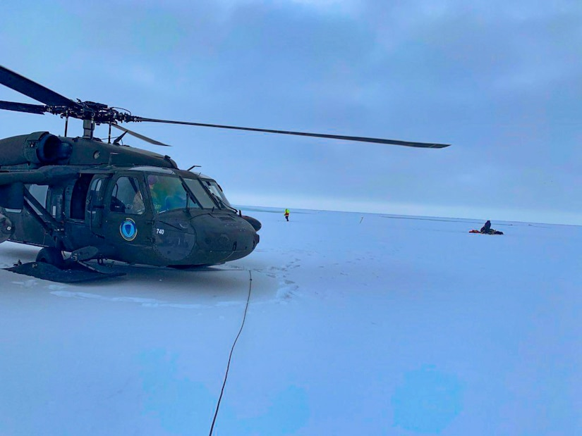 An Alaska Army National Guard UH-60 Black Hawk helicopter sits on packed snow about 25 miles east of Nome, Alaska, during a search and rescue mission for three Iditarod mushers March 20, 2020. The mushers and their dogs went through Bering Sea flood waters on the race trail and were wet and freezing. The aircrew transported two firefighter emergency medical technicians and Iditarod dog handlers to assist. The mushers were flown to Nome and transported to a local hospital. A local search and rescue team helped race dog handlers care for the sled team and returned them to Nome. (Courtesy photo)