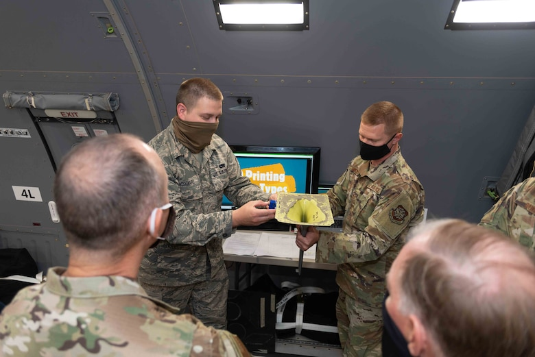 Staff Sgt. John Woodward and Tech. Sgt. Andrew Morrison, both 157th Maintenance Group, New Hampshire Air National Guard, demonstrate how in-house designed and 3-D printed plastic tools have the potential to save the Air Force hundreds of thousands of dollars and thousands of man-hours in maintaining the KC-46 to Brig. Gen. Richard Gibbs, Headquarters Air Mobility Command director of logistics, engineering and force protection, and Brig. Gen. Russell Ponder, National Guard Bureau director of logistics and installations, Sept. 9, 2020, at the Manchester-Boston Regional Airport in Manchester, New Hampshire. The 157th Air Refueling Wing is temporarily operating it's KC-46 refueling mission out of the civilian airport while the runway at the Pease International Airport is renovated from Sept. 8-22. (Air National Guard photo by Tech. Sgt. Aaron Vezeau)