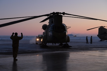 U.S. Soldiers with the Alaska Air National Guard assigned to the 2nd Battalion, 211th Aviation Regiment, help navigate CH-47 Chinooks into a hangar at Deadhorse, Alaska, Feb. 24, 2020. The Alaska National Guard is hosting Exercise Arctic Eagle 2020, a joint-training exercise, Feb. 20 to March 6, 2020, throughout Alaska, including Joint Base Elmendorf-Richardson, Eielson Air Force Base, Fort Wainwright, the Yukon-Kuskokwim Delta and as far north as Teshekpuk Lake. As a homeland security and emergency response exercise, Arctic Eagle 20 is designed to increase the National Guard's ability and effectiveness to operate in the extreme cold-weather conditions found in Arctic environments. (U.S. Air Force photo by Tech. Sgt. Amy Picard)