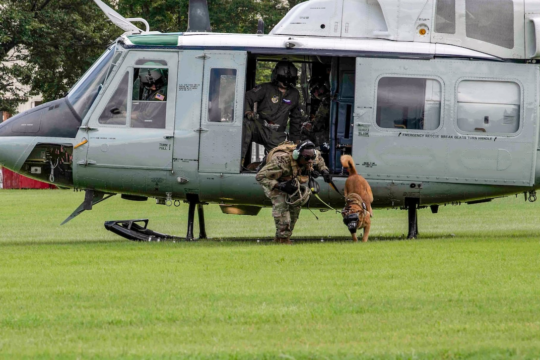 An airman and dog crouch as they move away from a helicopter parked in a grassy field.