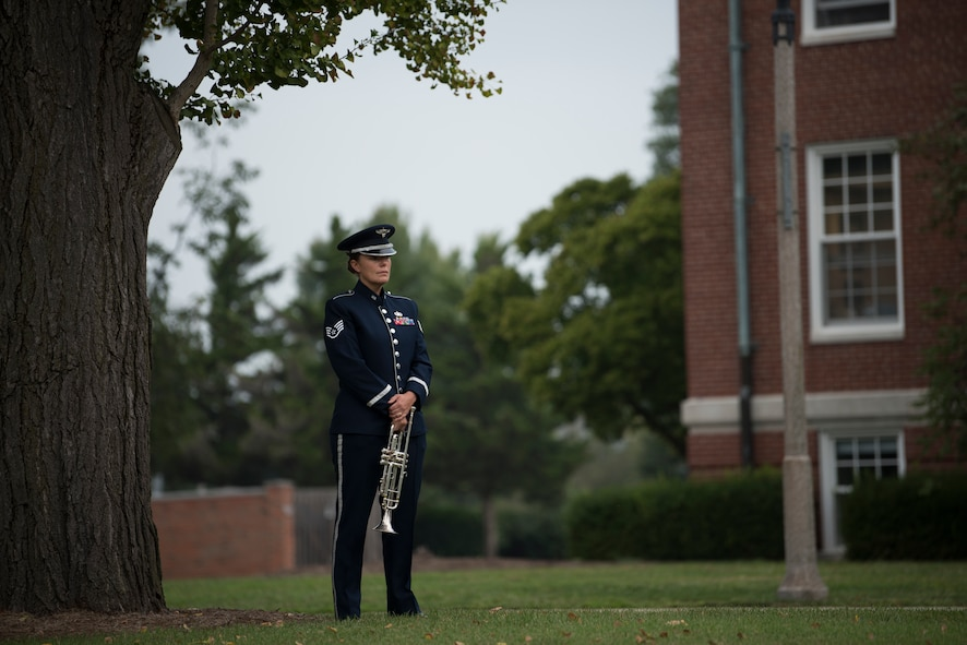 Airman stands under tree