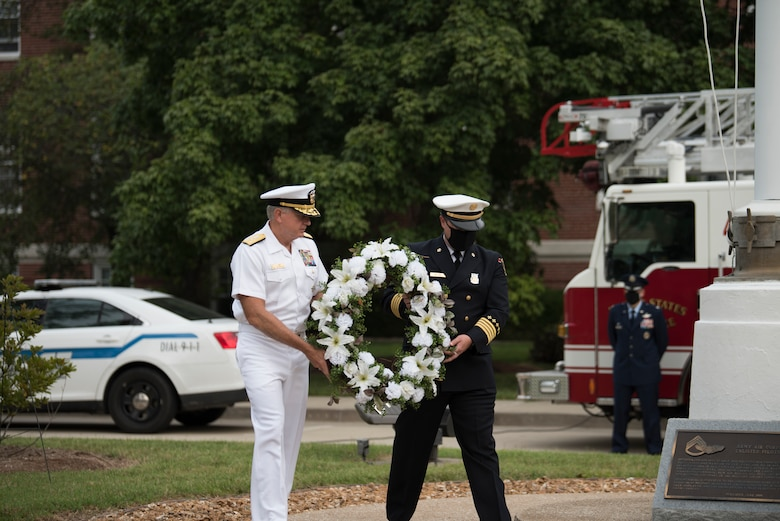 U.S. Navy Vice Admiral Dee L. Mewbourne, U.S. Transportation Command deputy commander, left, and Belland Eric Belland, 375th Civil Engineer Squadron fire chief, right, carry a wreath