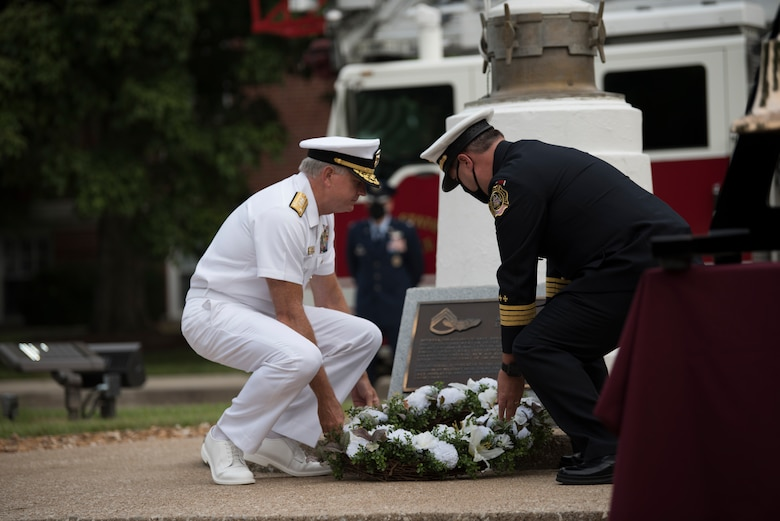 Service members lay wreath on ground