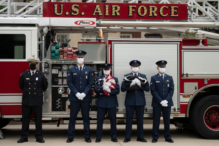 Service members stand in front of fire truck