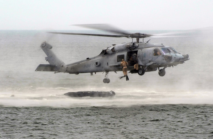 """U.S. Navy SEALs drop into the ocean from an HH-60H Seahawk helicopter of Helicopter Sea Combat Squadron 84 """"The Red Wolves"""" during a capabilities exercise, at Joint Expeditionary Base Little Creek"""