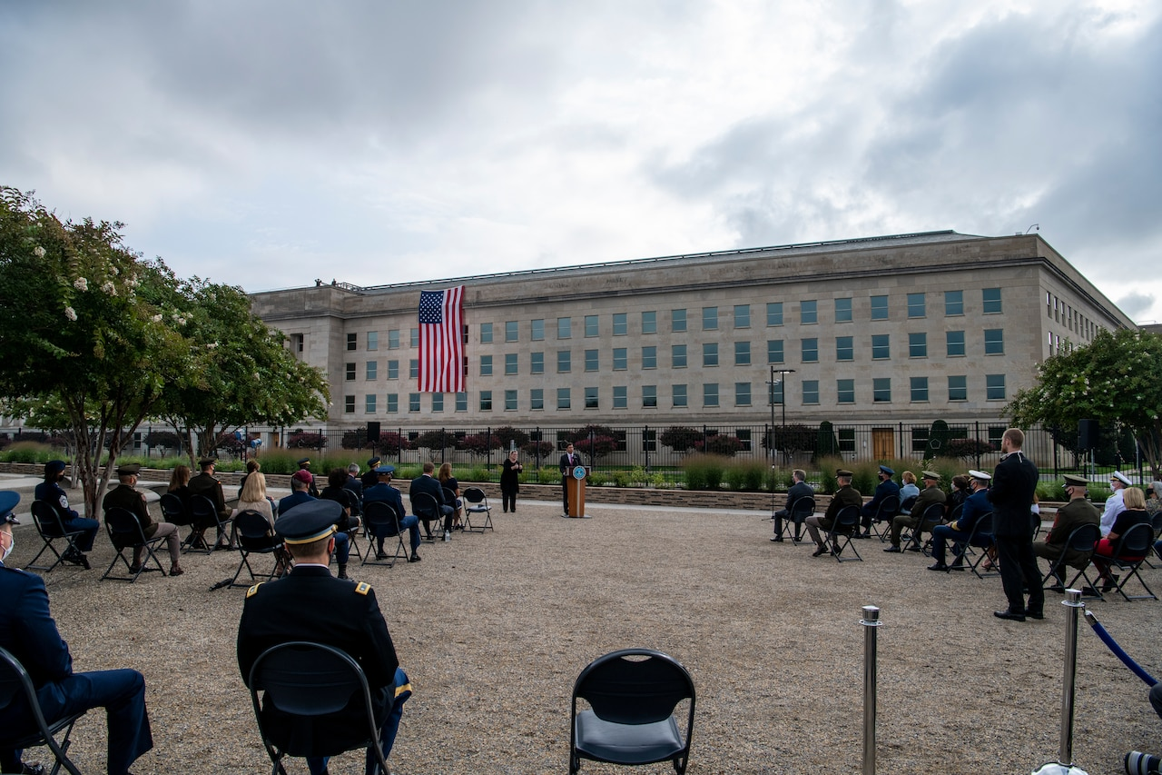 People sit outdoors and listen to someone at a podium; a large building is in the background.