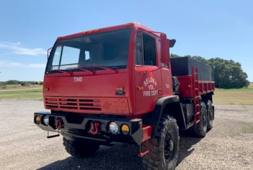 A former military truck with a red paint job sits on a gravel lot ready to help fight fires in Texas.