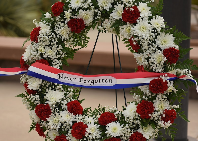 photo of a wreath with the words, never forgotten, displayed on a stand at a 9/11 remembrance ceremony