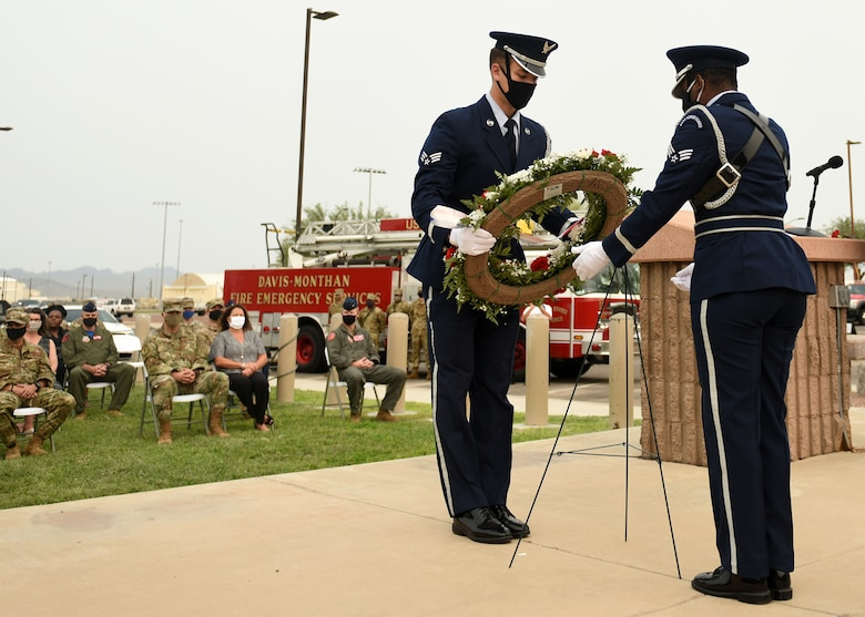 photo of two Air Force Honor Guard members placing a wreath for display during a 9/11 remembrance ceremony at Davis-Monthan Air Force Base, Arizona