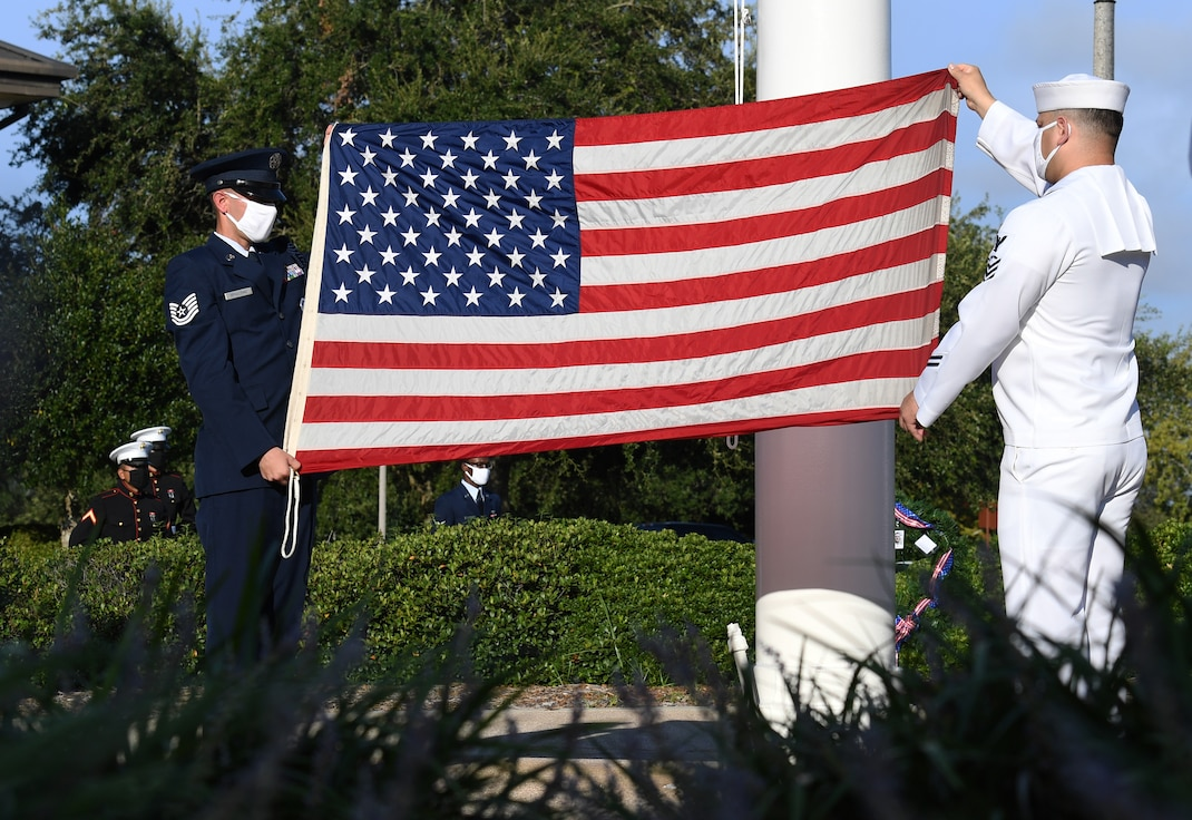 U.S. Air Force Tech. Sgt. Landon Spaulding, 81st Training Support Squadron military training leader, and U.S. Navy Aviation Electronics Technician 1st Class Javier Castoreno, Center for Naval Aviation Technical Training Unit Keesler instructor, display the U.S. flag during a 9/11 memorial ceremony hosted by the CNATTU Keesler in front of the 81st Training Wing headquarters building at Keesler Air Force Base, Mississippi, Sept. 11, 2020. The event honored those who lost their lives during the 9/11 attacks. (U.S. Air Force photo by Kemberly Groue)