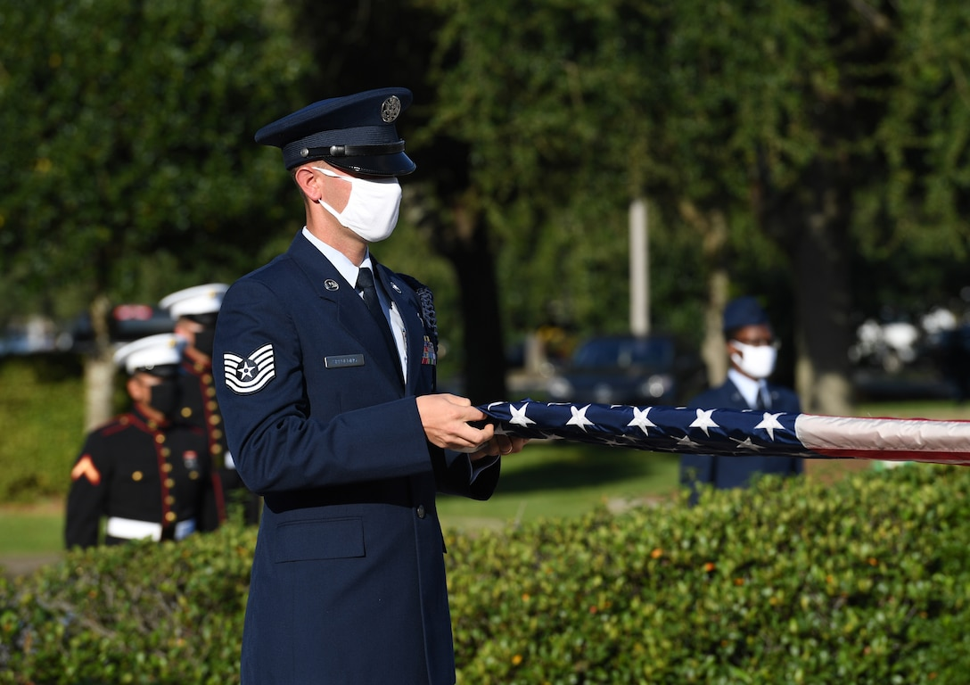 U.S. Air Force Tech. Sgt. Landon Spaulding, 81st Training Support Squadron military training leader, unfolds the U.S. flag during a 9/11 memorial ceremony hosted by the Center for Naval Aviation Technical Training Unit Keesler in front of the 81st Training Wing headquarters building at Keesler Air Force Base, Mississippi, Sept. 11, 2020. The event honored those who lost their lives during the 9/11 attacks. (U.S. Air Force photo by Kemberly Groue)