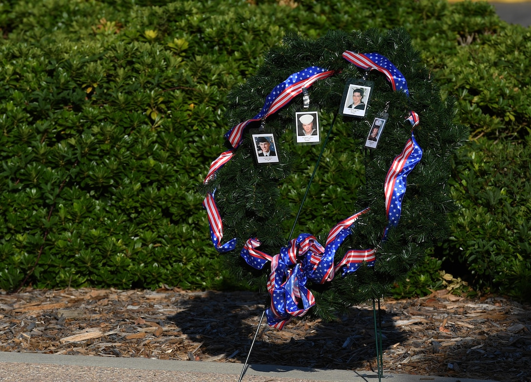A wreath displaying photo identification cards of military members who lost their lives in the 9/11 attacks are displayed during a 9/11 memorial ceremony hosted by the Center for Naval Aviation Technical Training Unit Keesler in front of the 81st Training Wing headquarters building at Keesler Air Force Base, Mississippi, Sept. 11, 2020. The event honored those who lost their lives during the 9/11 attacks. (U.S. Air Force photo by Kemberly Groue)