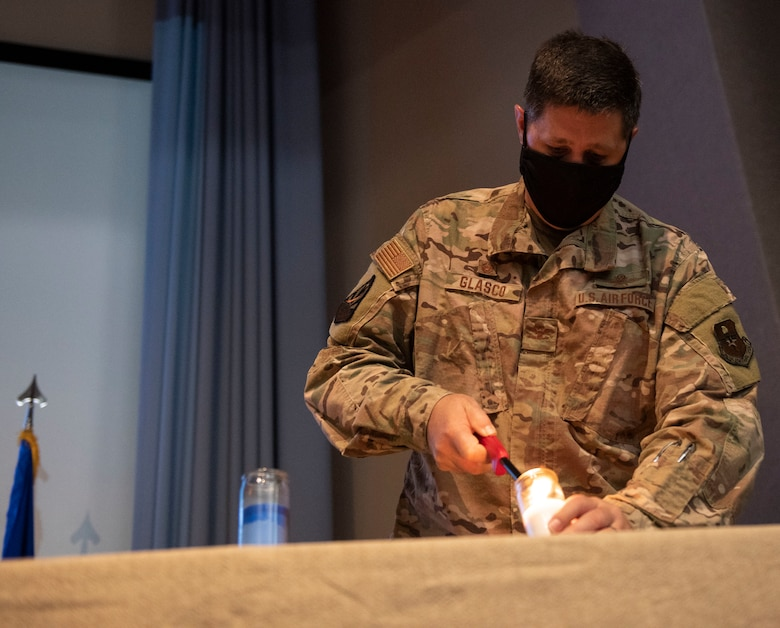 Col. Ted Glasco, 47th Mission Support Group commander, lights a white candle at the 9/11 Remembrance Ceremony on Sept. 11, 2020 at Laughlin Air Force Base, Texas. The white candle symbolizes the families who were touched by the 9/11 terrorist attacks.